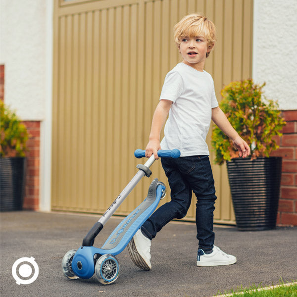 Kid pulls the Globber Primo Foldable Light three wheel scooter