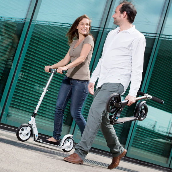 couple riding micro black and micro white kick scooter