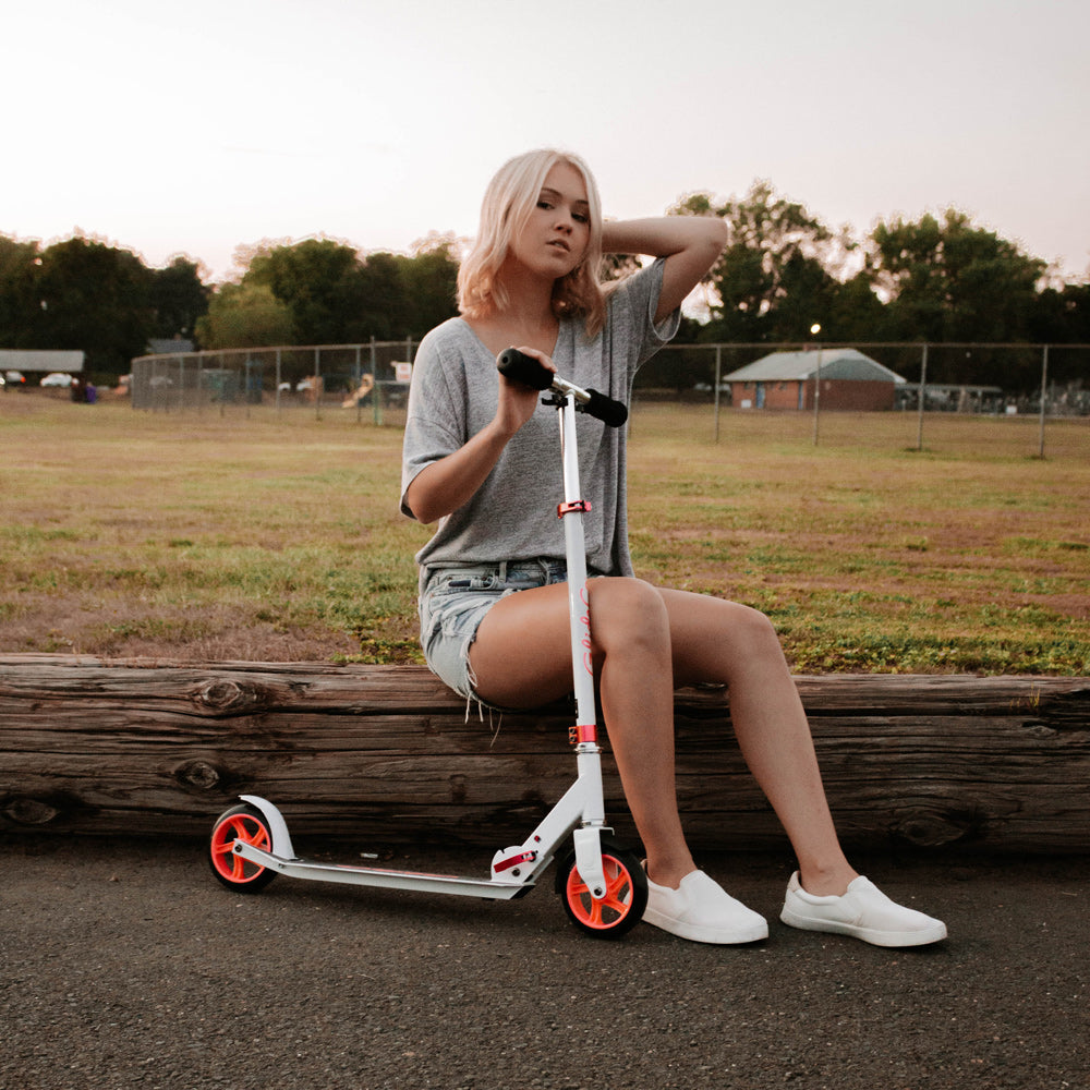 Girl sitting beside Glideco CityZipper145 kick scooter in white/pink