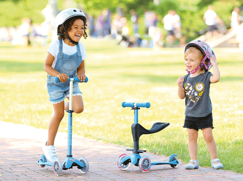 Girls riding Micro Mini 3in1 Deluxe plus in two different modes