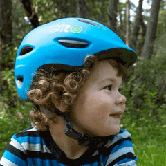 young boy wearing giro scamp bicycle helmet in blue