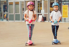Kids riding the Globber Primo Lights foldable kick scooter