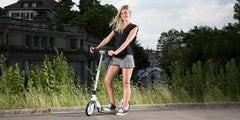 young woman standing with micro white kick scooter