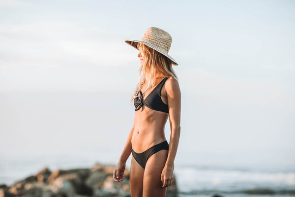 Woman standing on beach in montauk weraing the Biarritz knot front bikini top in ribbed midnight - summer label swimwear from montauk new york