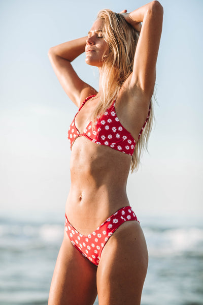 Woman standing in front of the ocean wearing the Byron bikini bottom in red daisy - Summer label swimwear.  The best bikinis for summer all year long.