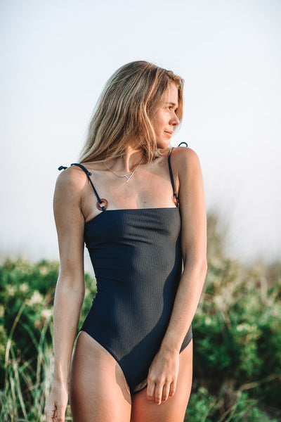 Woman at the beach wearing the Culebra One Piece Swimsuit in Ribbed Midnight- Summer Label