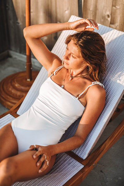 Woman lounging next to pool in the Culebra one piece swimsuit with tie shoulders in ribbed foam - Summer Label Swimwear