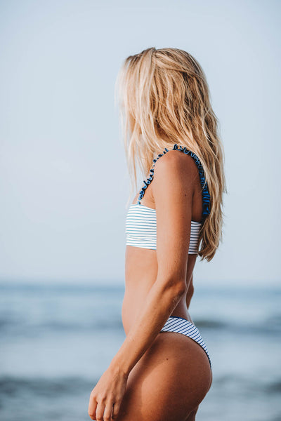 Blonde woman standing in front of ocean in Montauk New York wearing the Bahama Bandeau Bikini Top in Ocean Stripe - Summer Label