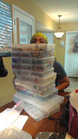 person wearing glasses barely visible behind stacks of bead storage boxes
