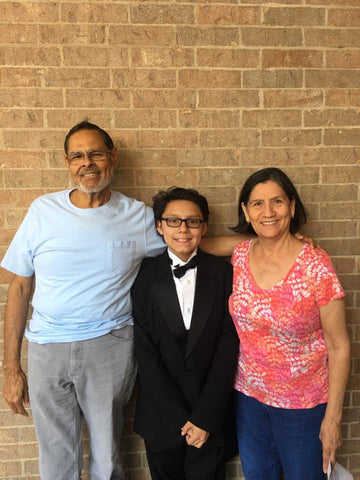 left to right: my dad about six feet tall, slender, beard, glasses, in the middle, my son, age 13, wearing a tuxedo from a band concert and far right, my mom, wearing a pink floral blouse and jeans