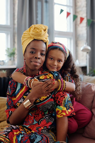 mom with yellow head wrap with vibrant colored fabric dress and daughter with bracelets and heandband