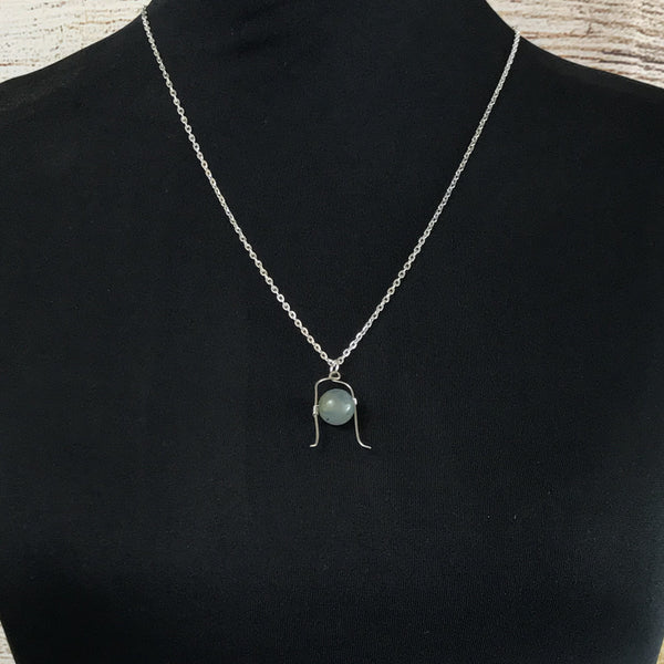 moss agate pendant necklace, silver tone cable chain necklace on a black covered bodice with faux wood background