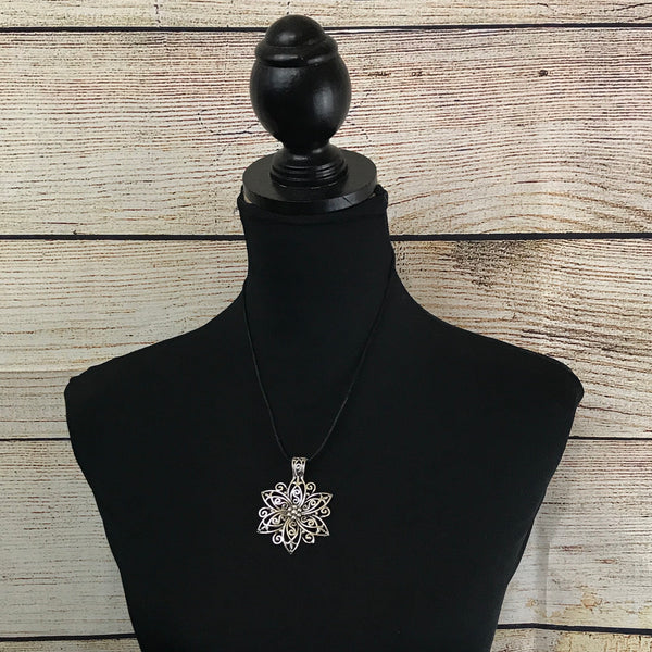 large silver flower pendant, black leather cord, silver tone findings, single strand necklace