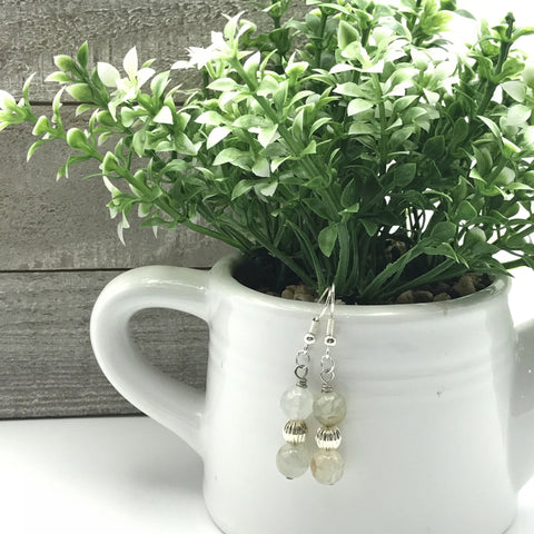 Light blue beaded dangle earrings with silver spacer beads and fish hook ear wires suspended from a white ceramic planter with a green and white succulent plant