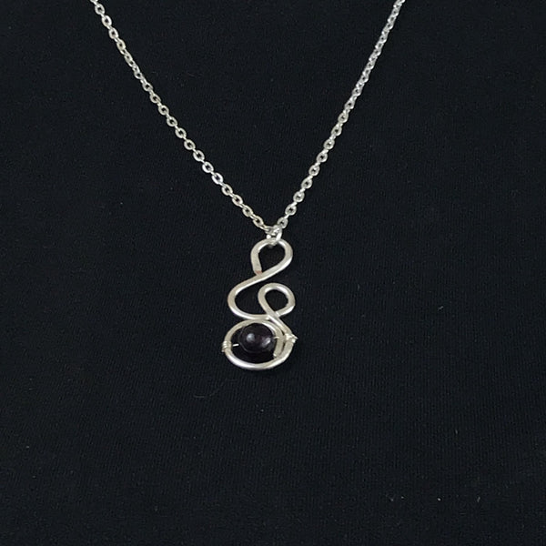 silver chain with pendant resembling a treble clef with purple glass bead wire wrapped on the tail of the treble clef