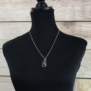 long silver chain with hand wired pendant with glass purple round bead pendant resembles a treble clef on dress bodice with black cover and a shiplap background