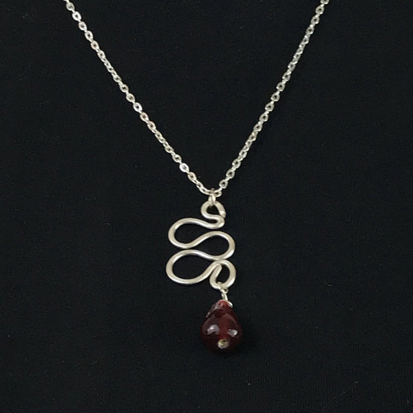 silver tone swirl charm with red glass teardrop bead suspended from a silver tone cable chain necklace