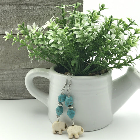 blue and white elephant earrings, white ceramic water can with green succulents, brown shiplap on a white background