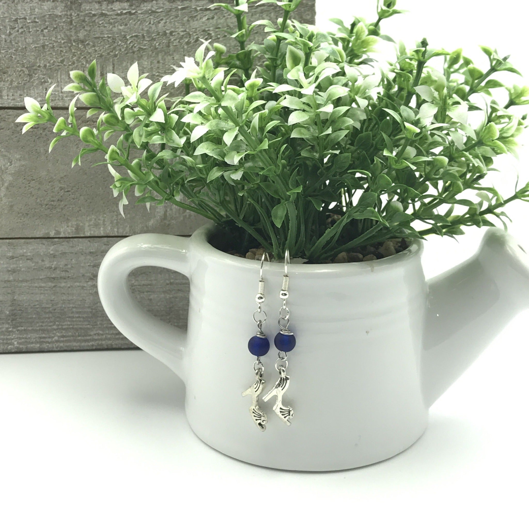 charming vintage silver tone high heel charm earrings with matte, blue, glass, round beads hung on a white ceramic watering can with a green and white tip succulent inside