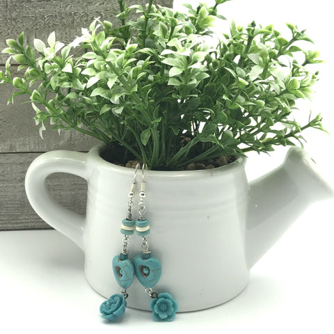 turquoise blue disc beads, blue hearts and blue flower earrings, white ceramic water can, green and white succulent plant, shiplap board in background, white background