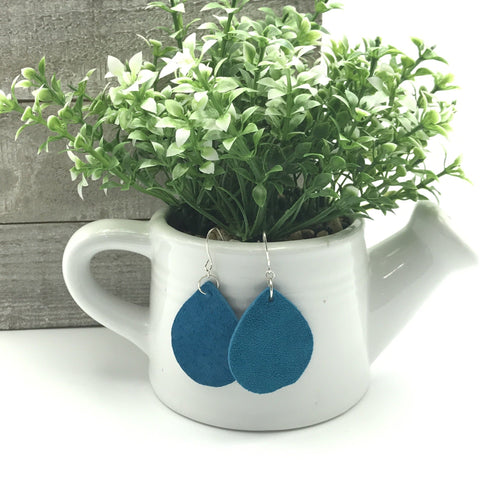 blue suede teardrop earrings dangle from a white ceramic water can holding a green and white faux succulent plant with shiplap background on white