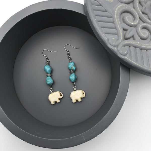 turquoise, silver, and white elephant beaded earrings on a gray jewelry box