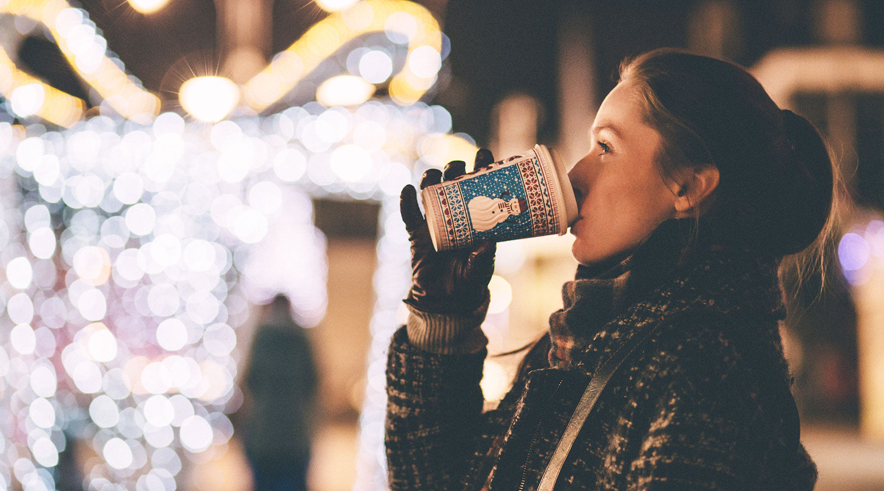 Woman drinking warm holiday drink looking at lights