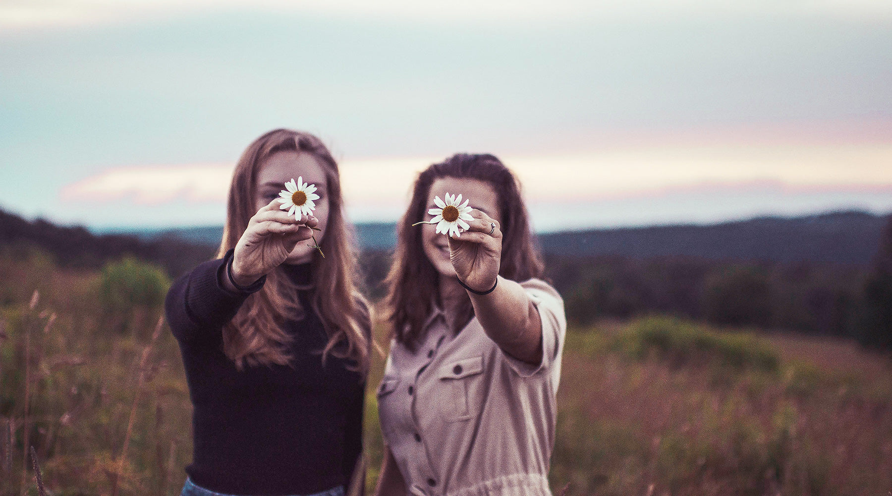 Two girls holding daisies in front of faces