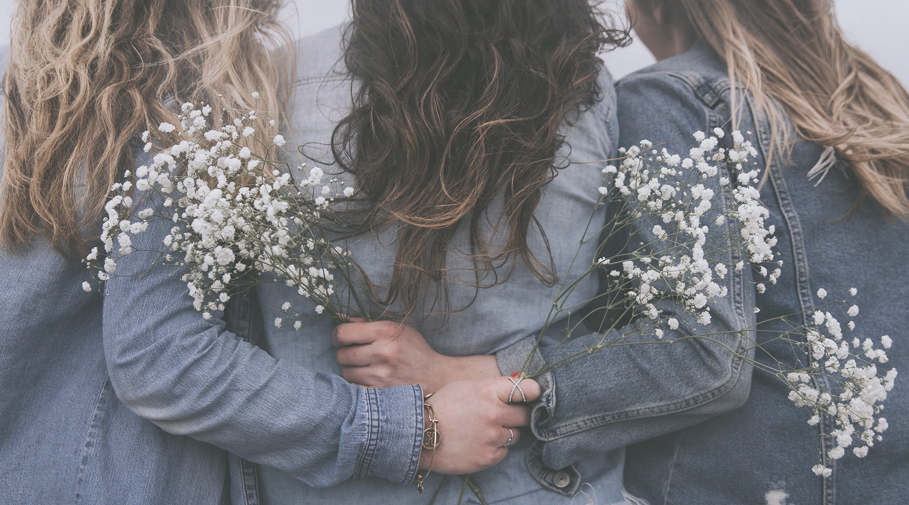 Women hugging and holding flowers