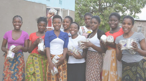 Group of women smiling and holding pad dontation