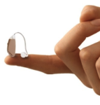 Image of a small behind the ear hearing aid on a fingertip