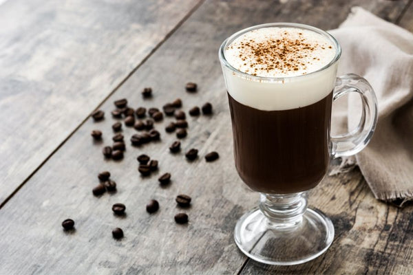 Irish Coffee Hot on table with whipped cream topping and cinnamon