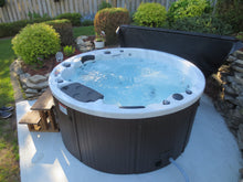 Load image into Gallery viewer, Ottawa 38-Jet 6-Person Spa. Description:Slow down and enjoy each other's company in a Canadian Spa Company Ottawa hot tub while 38 adjustable hurricane jets help to work out that knot in your back. This tub is perfect for any family as it fits 6-people comfortably. A powerful 16 amp 5HP 2 Speed pump and adjustable air valves ensure that everyone receives the pressure that they require.  The Ottawa hot tub features perimeter multi-coloured LED lighting and a Bluetooth Audio System.