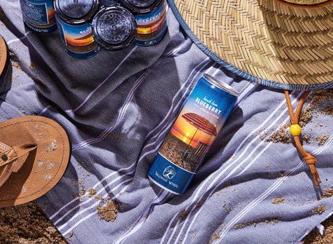 Beach Bum Blueberry sparkling wine can on a beach towel with sun hat, flip flops, and six pack of canned wine.