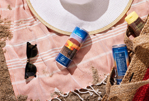 Beach Bum Blueberry sparkling wine can on the beach with sunglasses and beach hat.