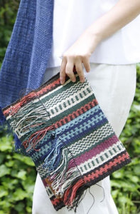 Close of up Woman holding Multicolored Chaguar Clutch Bag with Fringe Ends.
