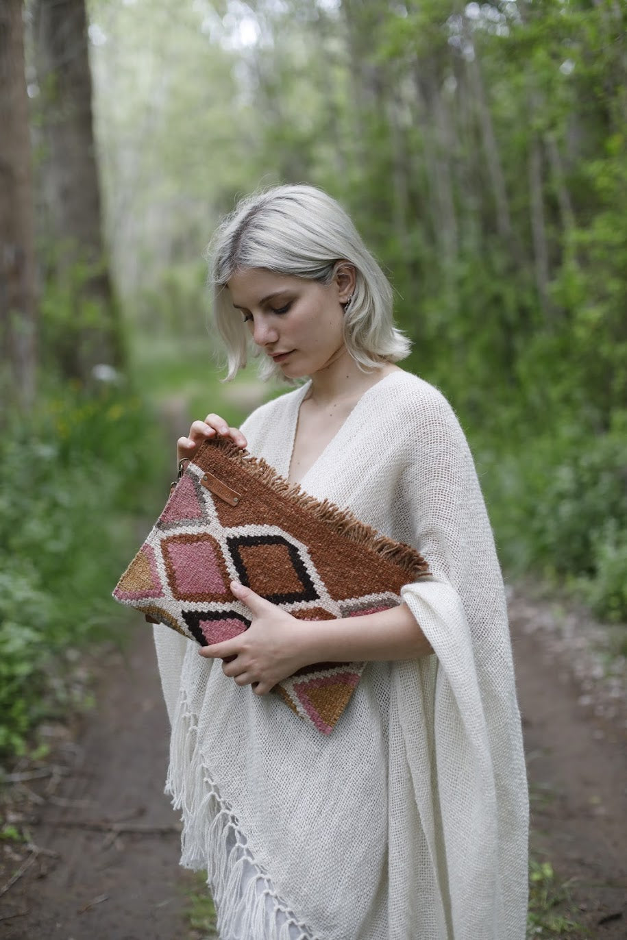 Woman holding Cream, Natural Brown, Pink, and Black Geometric Designed Clutch Bag.