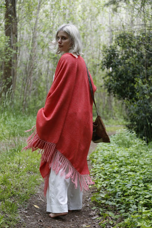 Woman wearing Red Llama and Cotton Poncho with long Fringe Ends.