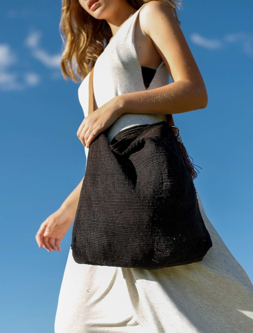 Close up of Woman holding Black Chaguar Purse with Brown Leather Strap.
