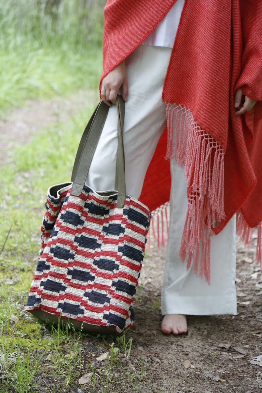 Close up of Woman holding Cream Suri Chaguar Purse with Red and Blue Design. Straps are Gray Leather.