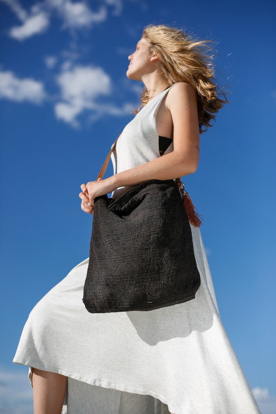 Woman holding Black Chaguar Purse with Brown Leather Strap.