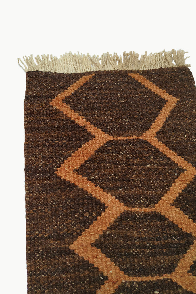 Close up of Dark Brown Special Size Wool Tapestry with Orange Designs and Cream Fringe Ends.