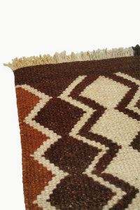 Close up of Dark Brown Special Size Wool Tapestry with Cream and Ochre Design details with Fringe ends.