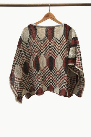 Cream Chaguar Poncho with Red and Black Hexagonal Design Details.