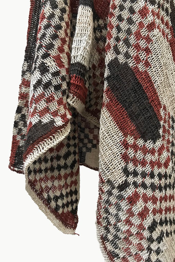 Close up of Cream Chaguar Poncho with Red and Black Hexagonal Design Details.