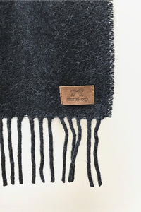 Close up of Black Llama and Sheep Wool Scarf. Wool Texture and Tag is shown.