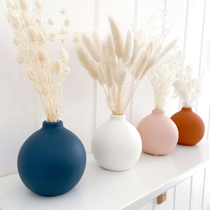 Four small round vases on a white nursery shelf with preserved flowers in them. Vases are in Navy, white, pink and terracotta. Ming Fern, Bunny Tail Grass, Valentine Grass and Sea Holly in each of the vases.