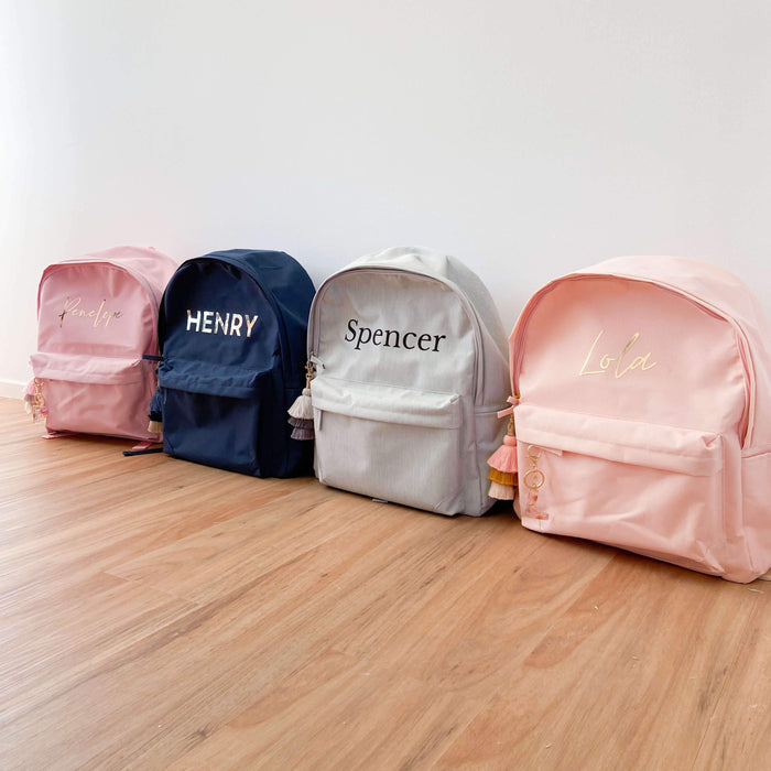 Personalised Kids Daycare Backpack in peach, pink, navy and light grey. The bags are personalised with names in gold, silver, rose gold and black. Ideal for school bags, daycare or kindy bags, everyday bag or travel bags.