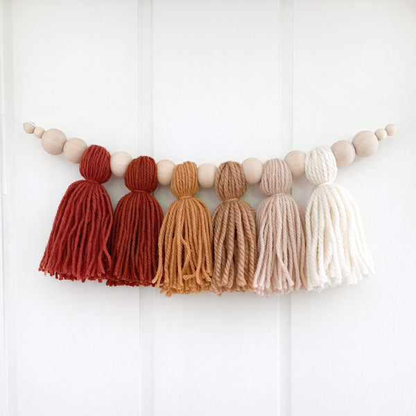 Image features Mini Minx Kids handmade yarn tassel garland in earthy tones hanging on white nursery wall.