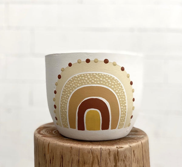 Image of the Mowgli Studio pot. The cream-coloured pot features a hand-painted rainbow in earthy tones and sits on a tree stump.